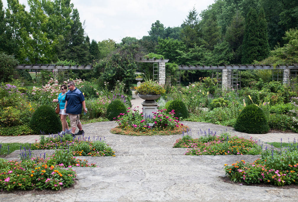... Roses Is The Backbone Of This Bed With A Mixture Of Annuals,  Perennials, Shrubs And Vines, All Embraced By A Traditional Arbor Of  Limestone And Timber.